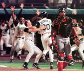 Cleveland Indians catcher Sandy Alomar walks off the feild as the Florida Marlins celebrate their 32 win in game seven of the World Series 26 October...