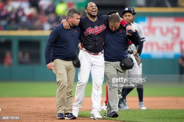Cleveland Indians designated hitter Edwin Encarnacion is in pain as he is helped from the field by members of the Indians medical staff after...