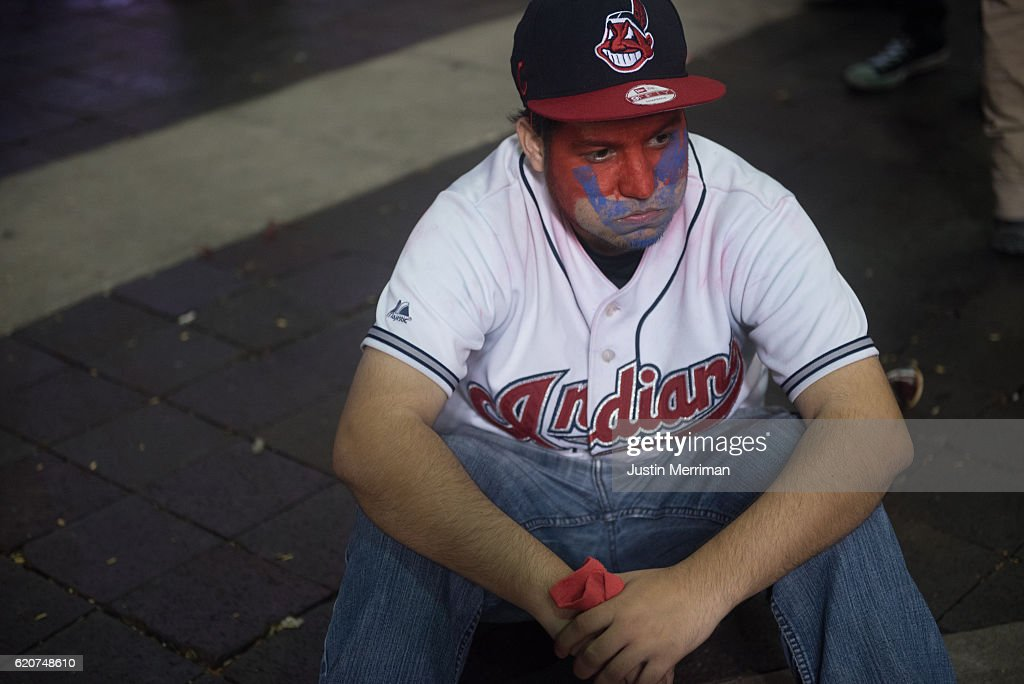 A Cleveland Indians fan sits in the street after the Chicago Cubs defeated the Cleveland Indians in game 7 of the World Series in the early morning hours on November 3, 2016 in Cleveland, Ohio. The Cubs defeated the Indians 8-7 in 10 innings for their first World Series championship in 108 years.