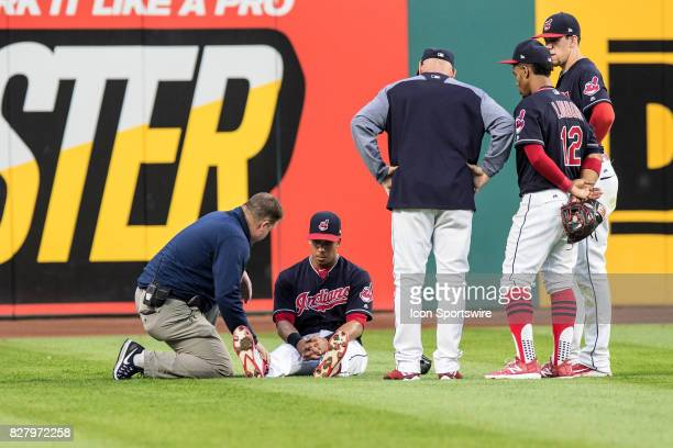 Cleveland Indians left fielder Michael Brantley is examined by a trainer after suffering an apparent lower body injury as Cleveland Indians manager...