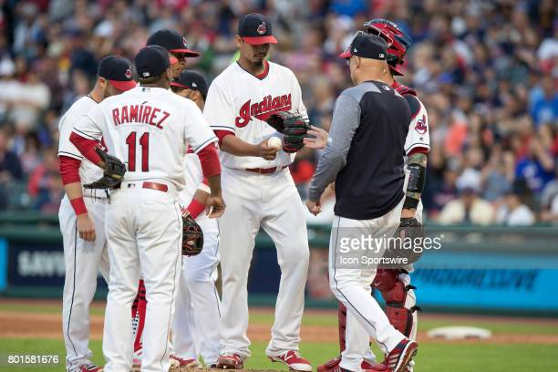 Cleveland Indians starting pitcher Carlos Carrasco hands the baseball to Cleveland Indians bench coach Brad Mills as he leaves the game during the...