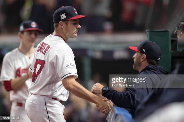 Cleveland Indians starting pitcher Trevor Bauer gets a handshake from Cleveland Indians pitching coach Mickey Callaway as he leaves the game during...