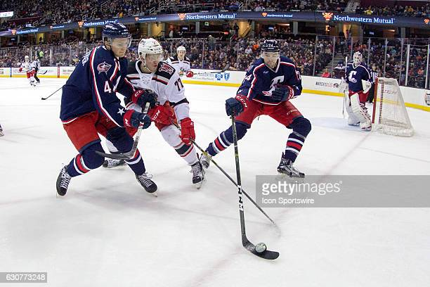 Cleveland Monsters D Oleg Yevenko clears the puck as Cleveland Monsters D Blake Siebenaler defends against Grand Rapids Griffins RW Evgeny Svechnikov...