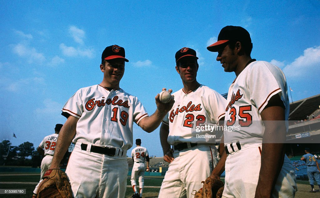 Pitching aces Mike Cuellar (35), Jim Palmer (22), and Dave McNally (19) of the Baltimore Orioles baseball team, in uniform in a baseball stadium.