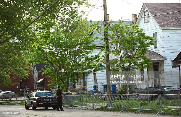 A Cleveland police officer stands watch in front of the house on Seymour Street where three women were held captive for a decade May 8 2013 in...