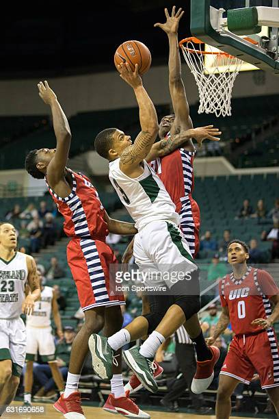 Cleveland State Vikings G Rob Edwards drives to the basket against UIC Flames G Tarkus Ferguson and UIC Flames F/C Tai Odiase during the first half...