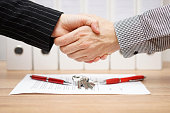 client and agent are handshaking over real estate contract and keys