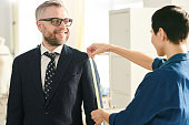Happy mature businessman in formalwear looking at professional tailor taking measures of his suit in workshop