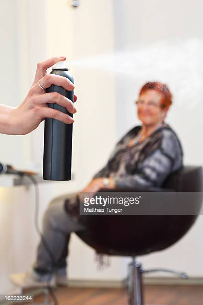 Client looking at a hairdresser's hand spraying