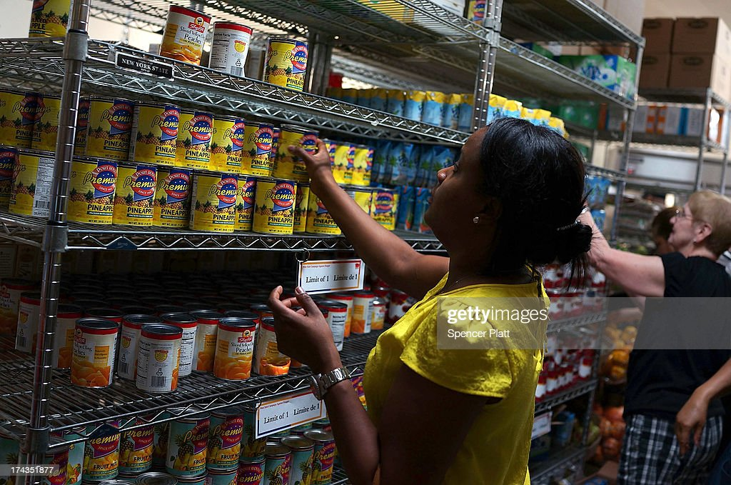 A client of the West Side Campaign Against Hunger food bank takes items from the shelf on July 24, 2013 in New York City. The food bank assists thousands of qualifying New York residents in providing a monthly allotment of food. In an anticipated speech today in Illinois, President Obama tried to re-focus the nation's attention back onto the economy and the growing inequality between the rich and the rest of America. As of May 2013 the unemployment rate in America was stuck at 7.6% with many more Americans having given up on looking for work.