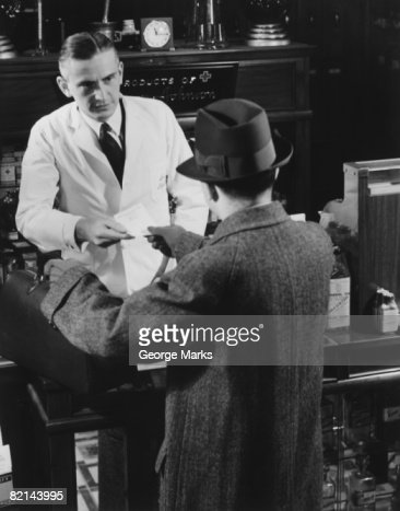 Client passing prescription to pharmacist, (B&W), elevated view : Bildbanksbilder