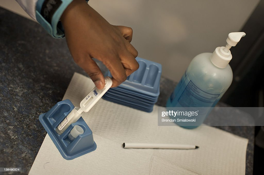 A client places an oral swab into a solution to complete an HIV test during a free HIV testing event at by the WhitmanWalker Health February 7 2012...