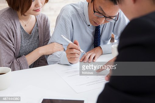 Client signing a real estate contract in real estate agency