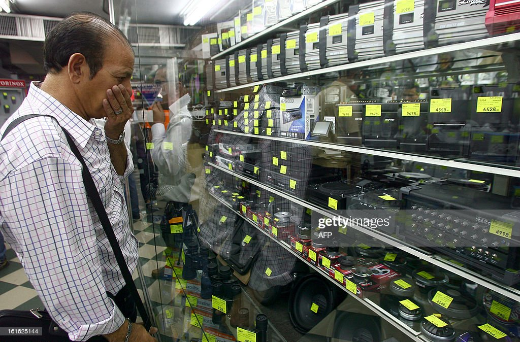 A client watches electronics at a store in Caracas on February 13, 2013. Venezuelans swamped stores on Tuesday to snap up everything from washing machines to plane tickets in a last-minute wave of panic-buying ahead of a 32 percent currency devaluation. AFP PHOTO/Geraldo CASO