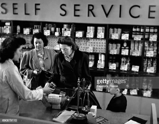 Cliente payant à la caisse ses courses qu'elle a faites dans un magasin en selfservice au RoyaumeUni