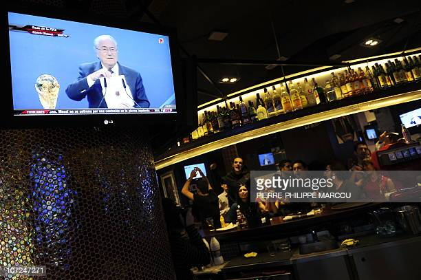 Clients and employees of a Sports bar in Madrid wait as they watch on a TV screen FIFA President Josef Blatter announcing officially the 2018 and...