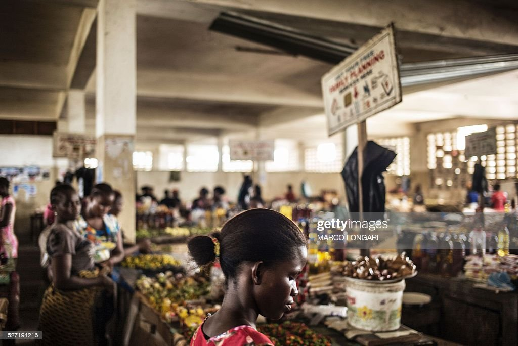 Clients are seen by stalls at the Jorkpan market at Sinkor district in Monrovia on May 2, 2016. Family planning services, like contraceptives and counselling are available in the markets in Liberia, an initiative that is aimed at tackling the high adolescent pregnancy rate in the younger population. / AFP / MARCO