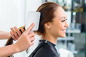 Hair brushing. Young appealing client is smiling while her hair is being brushed by a professional.