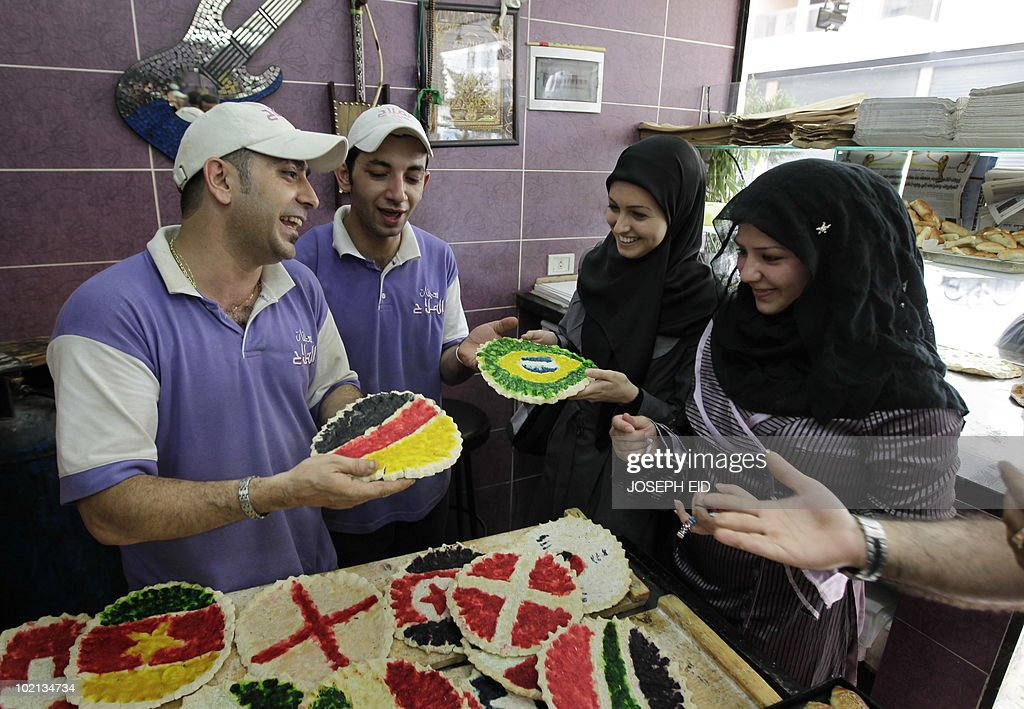 Clients inspect the 'special-edition World Cup 2010' traditional Lebanese oven-baked flat bread, covered with cheese and decorated with the flags of countries competing in the tournament, at a bakery in a southern suburb of Beirut on June 16, 2010.