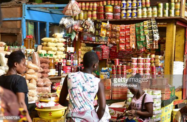 Clients look at stalls with various consumer products at the large market of Adjame a popular district of Abidjan on August 10 2017 The Ivorian...