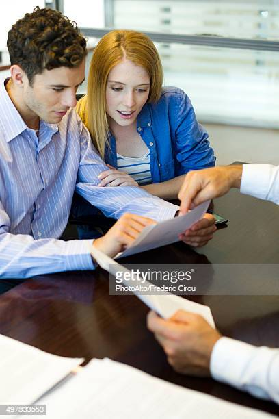 Clients looking at paperwork in office