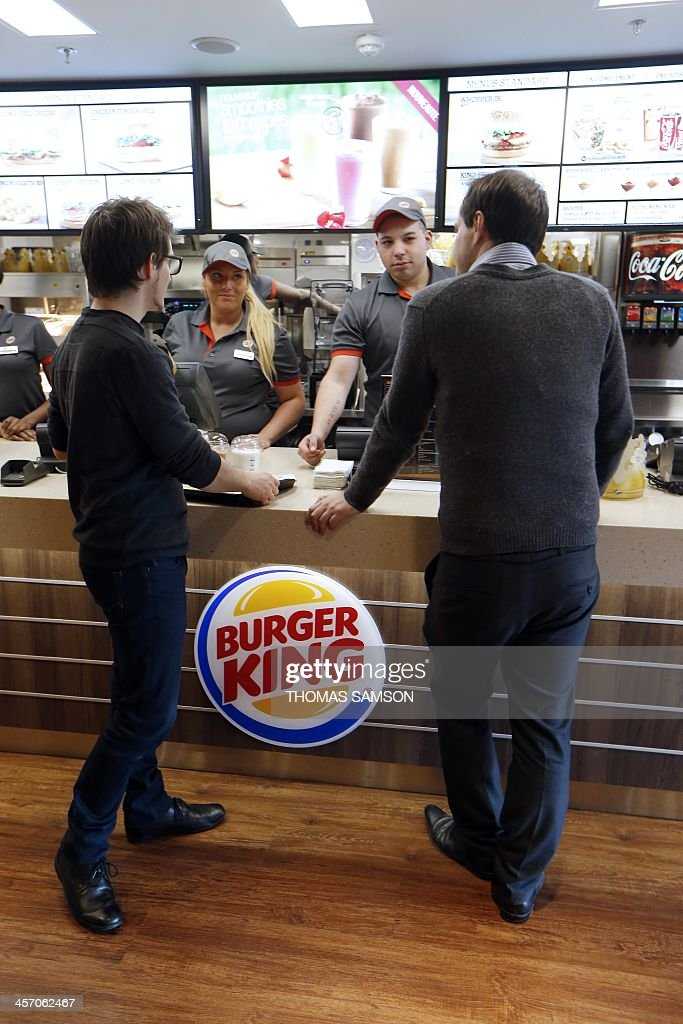 Clients order their meal at a Burger King store in Saint-Lazare railway station in Paris, on December 16, 2013, on its inauguration day. It is the fourth Burger King store to open its doors in France (the first in Paris), since the group returned in the country, last year.