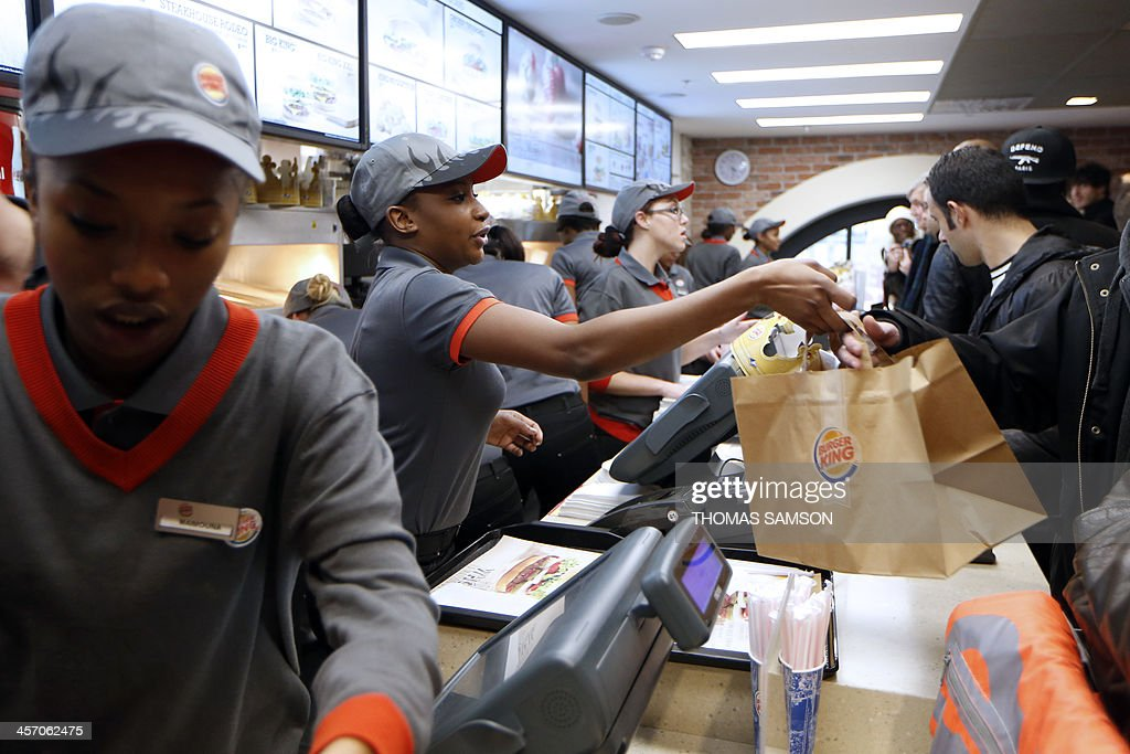 Clients order their meal at a Burger King store in Saint-Lazare railway station in Paris, on December 16, 2013, on its inauguration day. It is the fourth Burger King store to open its doors in France (the first in Paris), since the group returned in the country, last year. AFP PHOTO / THOMAS SAMSON