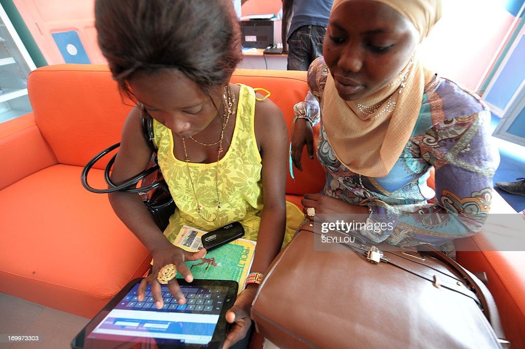 Clients use a tablet computer in the world's first cybercafe equipped with tablet computers in the Medina a popular district of Dakar on May 28 2013...