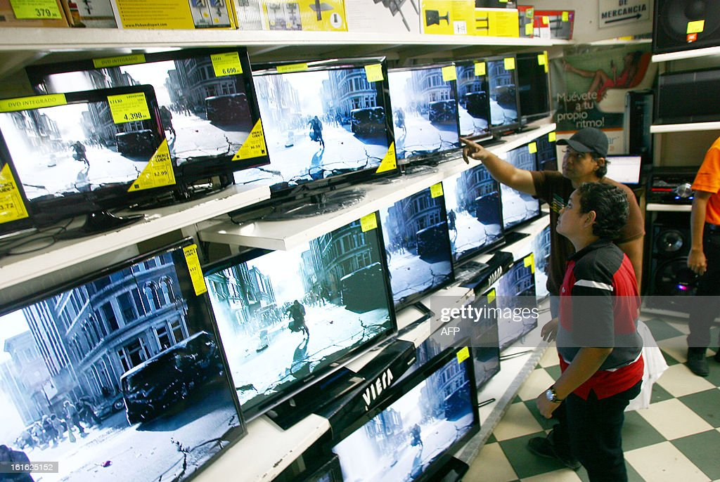 Clients watch digital televisions at a store in Caracas on February 13, 2013. Venezuelans swamped stores on Tuesday to snap up everything from washing machines to plane tickets in a last-minute wave of panic-buying ahead of a 32 percent currency devaluation. AFP PHOTO/Geraldo CASO