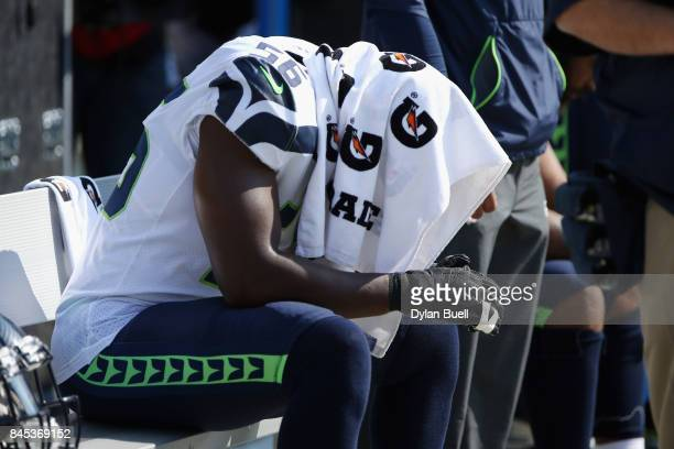 Cliff Avril of the Seattle Seahawks sits on the bench during the national anthem prior to the game against the Green Bay Packers at Lambeau Field on...