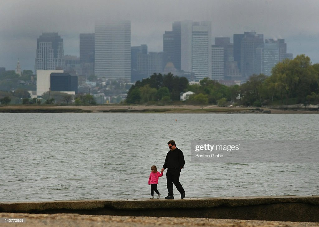 Cliff Edwards from Quincy walks along a breakwater on Wollaston Beach with his daughter, Sophia, 4, as clouds hang over the city of Boston in the early afternoon.