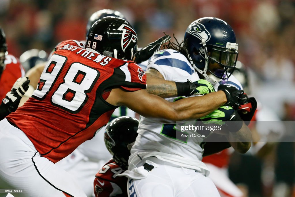 Cliff Matthews #98 of the Atlanta Falcons tackles Marshawn Lynch #24 of the Seattle Seahawks during the NFC Divisional Playoff Game at Georgia Dome on January 13, 2013 in Atlanta, Georgia.