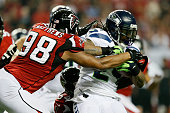 Cliff Matthews of the Atlanta Falcons tackles Marshawn Lynch of the Seattle Seahawks during the NFC Divisional Playoff Game at Georgia Dome on...