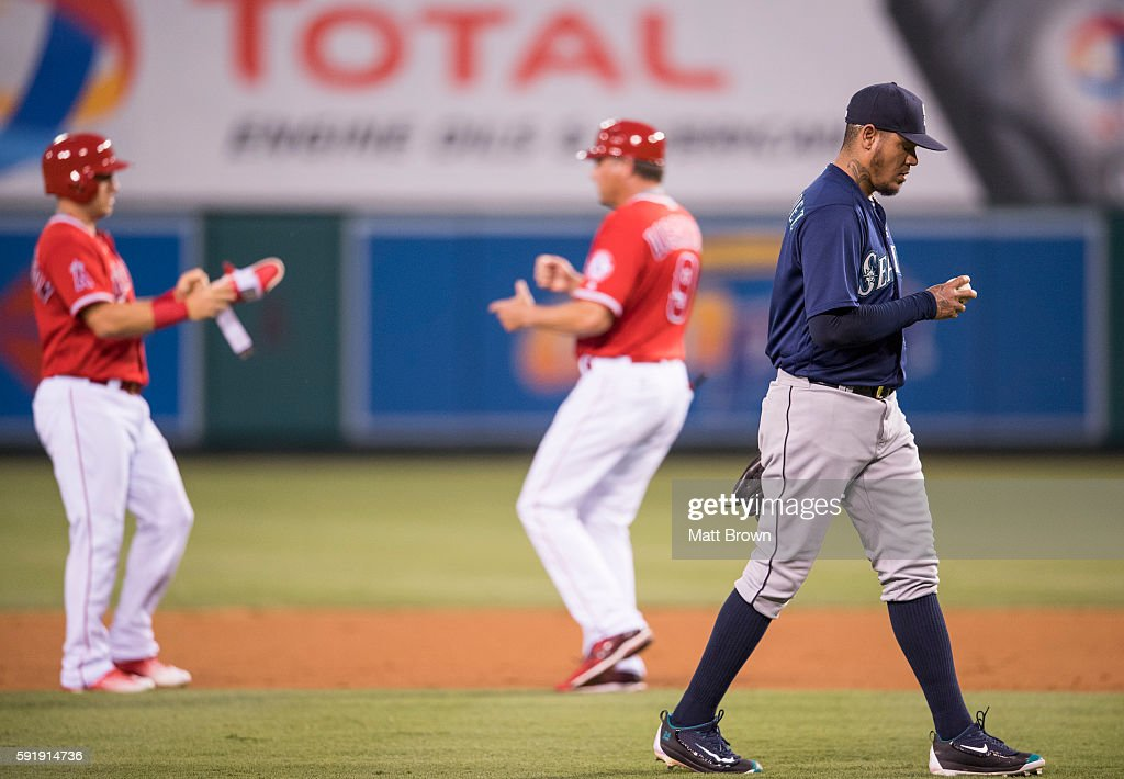 Cliff Pennington hands a guard to third base coach Gary Disarcina as starting pitcher Felix Hernandez of the Seattle Mariners reacts after Pennington...