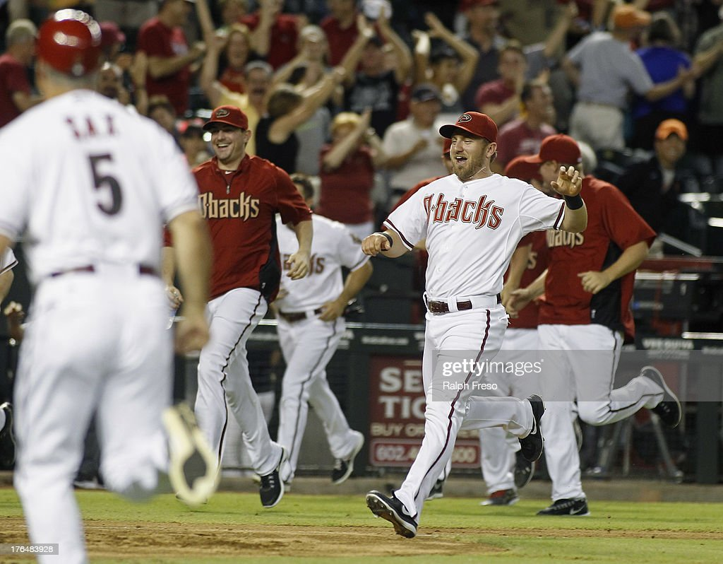 Cliff Pennington #4 of the Arizona Diamondbacks and teammates run onto the field to congratulate Paul Goldschmidt #44 following his game-winning walk off home run against the Baltimore Orioles in the eleventh inning of a MLB game at Chase Field on August 13, 2013 in Phoenix, Arizona. The Diamondbacks defeated the Orioles 4-3.