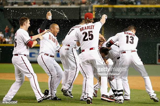 Cliff Pennington of the Arizona Diamondbacks is congratulated by Danny Dorn Yasmany Tomas Archie Bradley Nick Ahmed and Welington Castillo after...