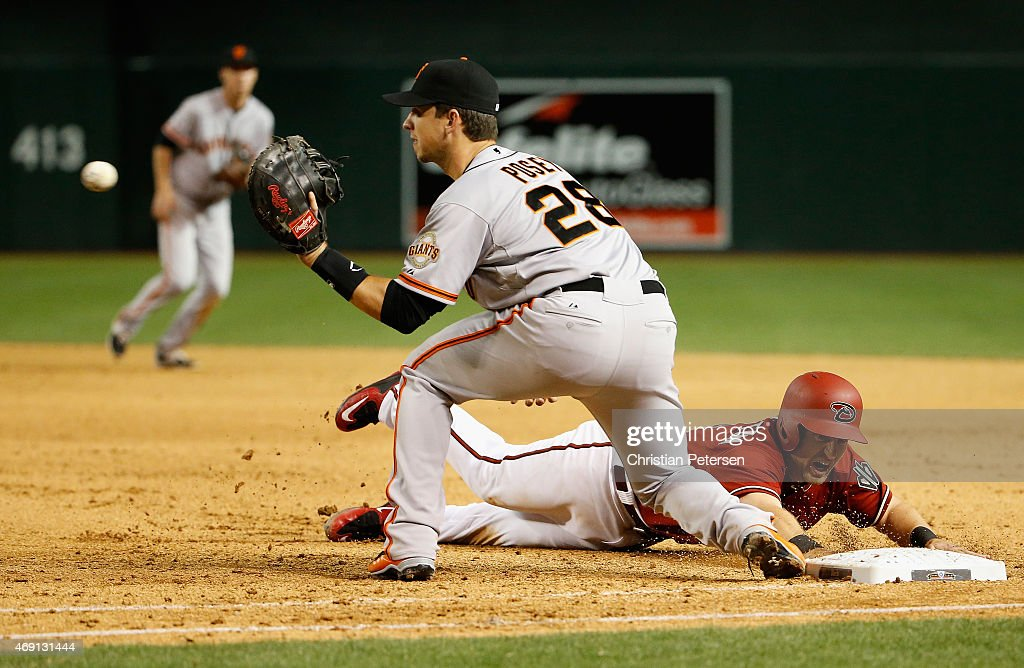 Cliff Pennington of the Arizona Diamondbacks slides back to first ahead of infielder Buster Posey of the San Francisco Giants during the MLB game at...