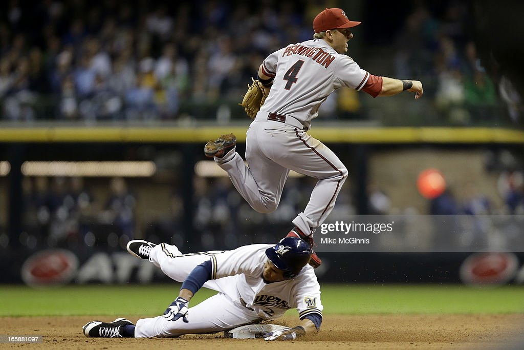 Cliff Pennington #4 of the Arizona Diamondbacks turns the double play while Carlos Gomez #27 slides into second base during the bottom of the sixth inning against the Milwaukee Brewers at Miller Park on April 6, 2013 in Milwaukee, Wisconsin.