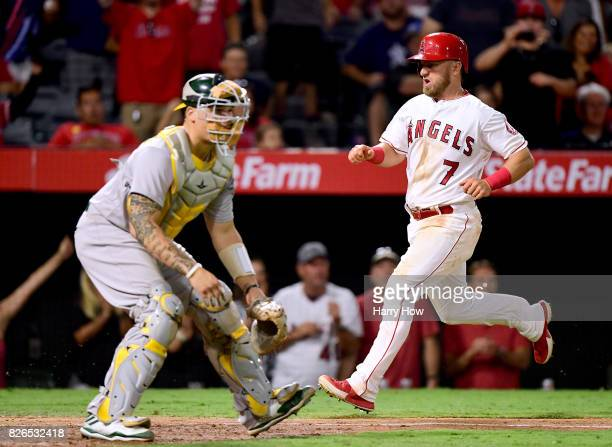 Cliff Pennington of the Los Angeles Angels scores behind Bruce Maxwell of the Oakland Athletics on a Mike Trout single for a 86 lead during the...
