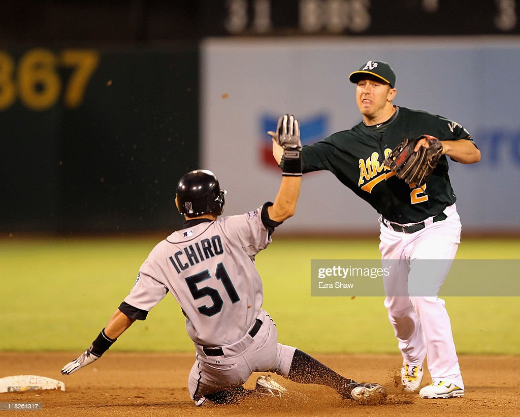 Cliff Pennington of the Oakland Athletics attempts to turn a double play against the Seattle Mariners Ichiro Suzuki of the Seattle Mariners slides in...