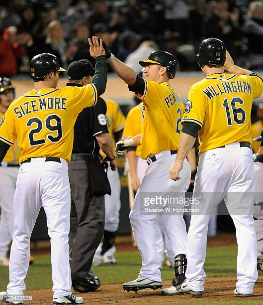 Cliff Pennington of the Oakland Athletics celebrates with Scott Sizemore and Josh Willingham after hitting a threerun home run against the Seattle...