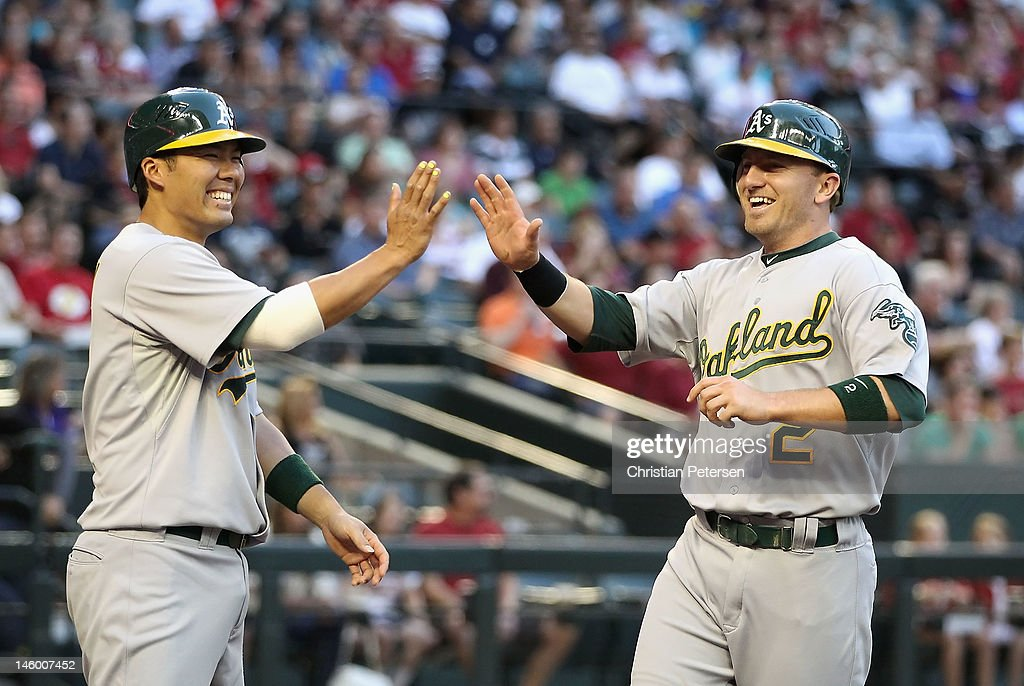 Cliff Pennington #2 of the Oakland Athletics high-fives Kurt Suzuki #8 after scoring against the Arizona Diamondbacks during the second inning of the interleague MLB game at Chase Field on June 8, 2012 in Phoenix, Arizona.