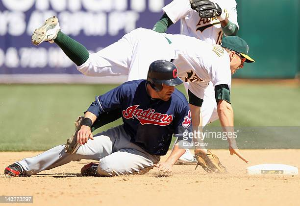 Cliff Pennington of the Oakland Athletics stumbles over Jason Kipnis of the Cleveland Indians after Pennington threw the ball to first base to...