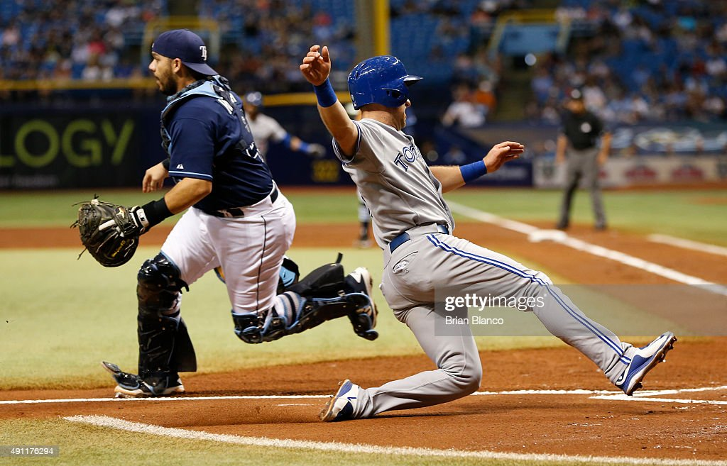 Cliff Pennington of the Toronto Blue Jays slides safely into homeplate ahead of catcher Rene Rivera of the Tampa Bay Rays to score off of an RBI...