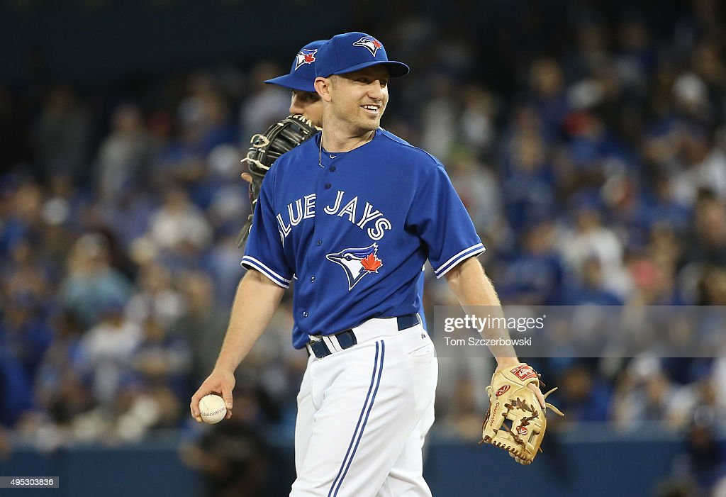 Cliff Pennington of the Toronto Blue Jays smiles while pitching in the ninth inning against the Kansas City Royals during game four of the American...