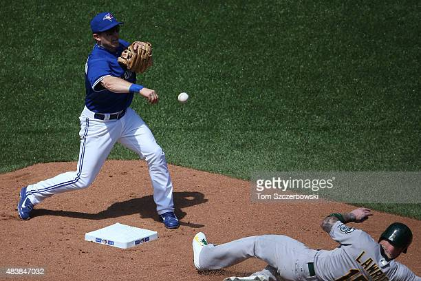 Cliff Pennington of the Toronto Blue Jays turns a double play in the sixth inning during MLB game action as Brett Lawrie of the Oakland Athletics...