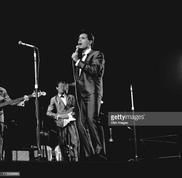 Cliff Richard performs on stage with The Shadows Hank Marvin behind 1961
