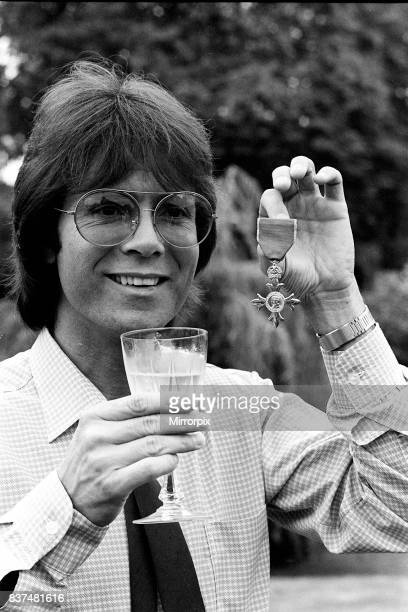 Cliff Richard with his OBE medal award drinkng wine 1980