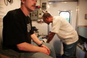 Cliff Sanchez a phlebotomist with the Chicago Recovery Alliance questions an intravenous drug user before testing him for HIV antibodies inside one...