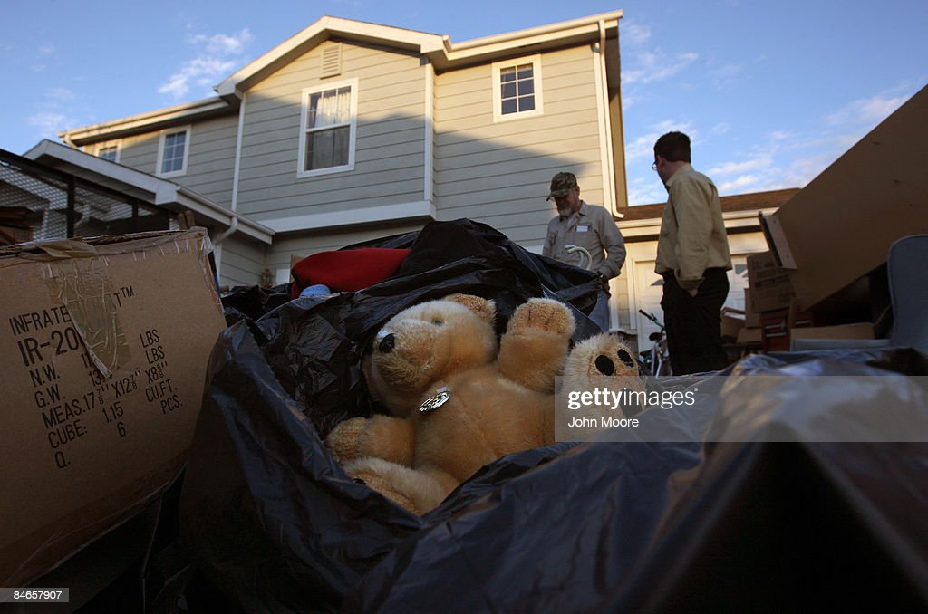 Clifford Coburn (L), looks over his belongings with a neighbor after he and his mother were evicted from their foreclosed home February 3, 2009 in Brighton, Colorado. Coburn owned the home for two years, living there with his mother and earlier with his now ex-wife and her five children. He said that he was laid off from his telecommunications job, and when he got new employment late last year, it paid only half the salary. He got behind in his mortgage payments and the bank ordered his eviction.